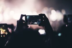 person filming concert on phone