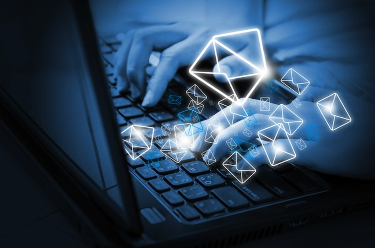person typing on computer with email icons